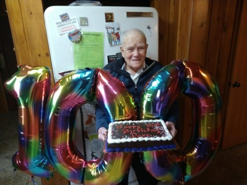 """Dave Armstrong holds his birthday cake and """"100"""" balloon on his 100th birthday recently.  Photo provided to Independent Record"""