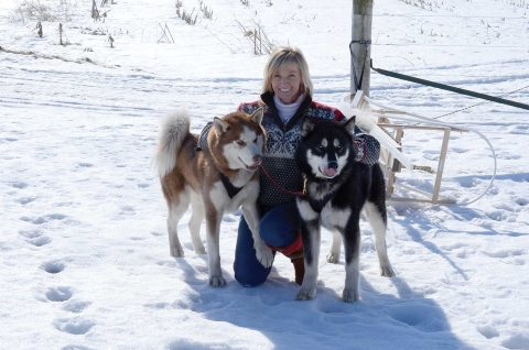 Dawn Prahl poses with two of the family's four Siberian huskies. On the left is Aspen, and Sequoia is on the right.