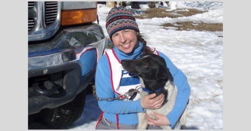 Mary Beth Logue hugs Bonanza, one of her Alaskan husky sled dogs. Photo provided.