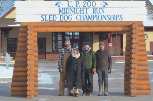 From left, U.P. 200 trail boss Mike Sjolund, Upper Peninsula Sled Dog Association Board members Angela Sjolund and Ross Anthony, and trail crew member Trevor Slinkard are shown with the UP200 starting gate that UPSDA officials set up at the Marquette Commons Thursday. The group did so to honor and recognize what would've been the 32nd running of the UP200, Midnight Run and Jack Pine 30 races this weekend, as they were canceled due to COVID-19. The 32nd running of the event has been postponed to 2022. The gate will be up through the weekend. (Journal photo by Ryan Spitza)