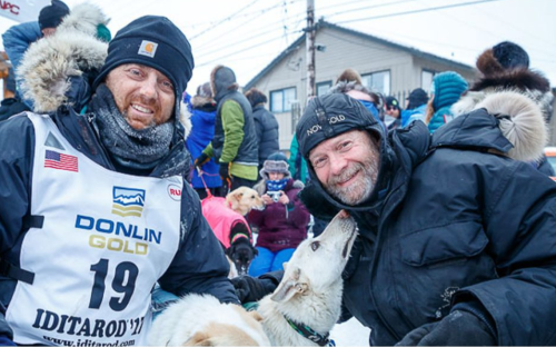 Gunnar Johnson at the Iditarod finish line in 2017 with his lead dogs Delta and Queen, along with the dogs
